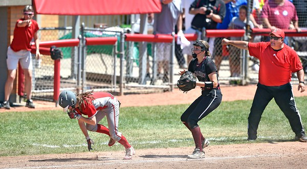 Elyria coach Ken Fenik, right, signals obstruction as Pioneer baserunner Macy Taylor tries to stay on her feet after colliding with Lebanon third baseman Alex Gibson. DAVID RICHARD / CHRONICLE