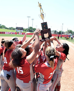 Elyria softball players hold up the state championship trophy Saturday in Akron. DAVID RICHARD / CHRONICLE