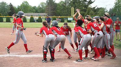 April Howser (25) heads for the plate to her cheering teammates after a two-run homer gave Elyria a commanding lead late. BRUCE BISHOP / CHRONICLE