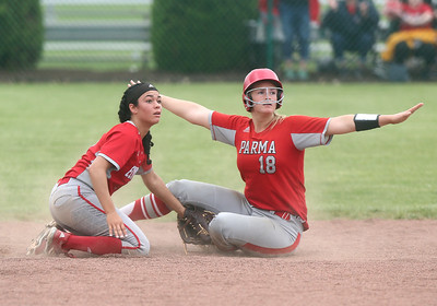 Elyria's Dierra Hammons (17) and Parma's Andrea Scali (18) both look to the umpire for the call after a close call at the plate. BRUCE BISHOP / CHRONICLE