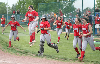 Elyria players can't wait to get to home plate to greet April Howser after she hit a two-run home run in the seventh inning of Wednesday's 6-2 win over Parma in a Division I regional semifinal.  BRUCE BISHOP / CHRONICLE