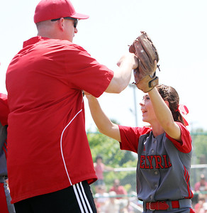ANNA NORRIS/CHRONICLE Elyria's Mackanzie Phares high-fives assistant coach John Wallace in the fifth inning against Brecksville in the regional championship game Saturday at Clyde High School.