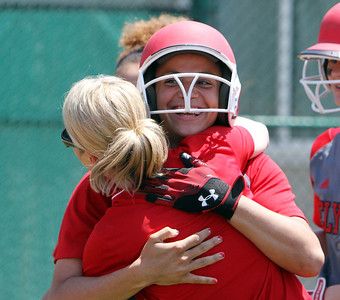 ANNA NORRIS/CHRONICLE Elyria's Kaitlyn Laseke smiles as she hugs assistant coach (need name) after hitting her second home run  in the Division I regional championship game against Brecksville Saturday afternoon. The Lady Pioneers won the game 4-0, advancing to the state tournament for the eighth time in nine years.