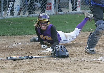 Avon's Brittnay Fowler works her way around Midview catcher Heather Miller and scores with the help of a high throw to the plate.  photo by Chuck Humel