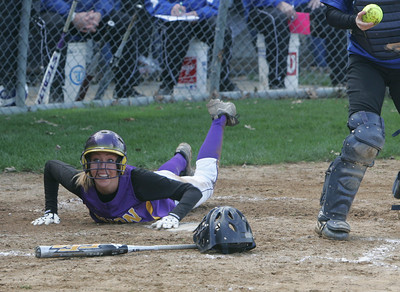 Avon's Brittnay Fowler works her way around Midview catcher Heather Miller and scores with the help of a high throw to the plate and looks to team mates to deliver the call of 'safe at the plate'.  photo by Chuck Humel