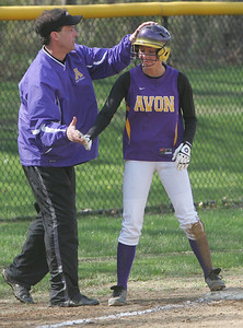 Avon's #18 Brittnay Fowler [check spelling on Brittnay] winds up on third base after a hit and an error and is congradulated by her coach.    photo by Chuck Humel