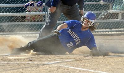 Midview's Amanda Beursken slides safe at home in first inning.  Steve Manheim