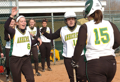 Amherst #15 Taylor Muhic is greeted at home plate by teammates after hitting a home run.