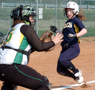 OF's #3 Kim Kirkpatrick slides safely into home as Amherst's catcher #15 Taylor Munic waits for the ball.