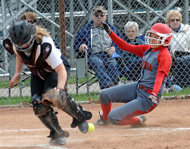 Elyria's Alex Dick slides in to home safely past Medina catcher Morgan Rittenhouse in the second inning Monday at Medina. STEVE MANHEIM/CHRONICLE