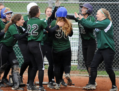 Westlake players congratulate Rachel May (30) as she crosses home plate after hitting a three-run home run in the third inning Friday against Amherst. The Demons won, 4-3. STEVE MANHEIM/CHRONICLE