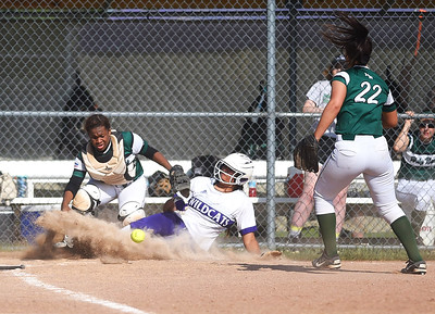 KRISTIN BAUER | CHRONICLE Keystone High School's Sammie Stefan (24) slides into home plate to score a run as Holy Name catcher Annessa Whitlow (47) fails to secure the ball in time on Thursday evening, May 18.