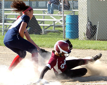 Wellington's #3 Amy Scaggs slides safely home before Oberlin's pitcher, #3 Katlyn Curtis-Campbell, can apply the tag.