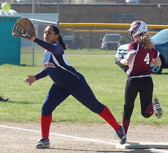 Wellington's #4 Karly Bollin is safe at first as Oberlin's #10 Maya Hicks waits for the ball.