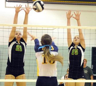 Amherst 21 Mallory Sliman and 15 Morgan Dziak defend against Olmsted Falls Abby Davison Oct. 4.  Steve Manheim