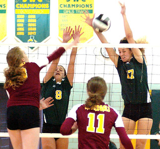 9-6-11 linda murphy  AL's #13 Isabelle Wagner tries to spike the ball past Amherst's #8 Riley Schenk & #17 Marie Concheck.