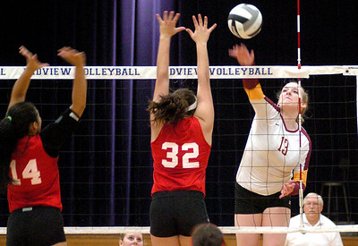 Avon Lake's #13 Isabelle Wagner spikes the ball past Elyria's #14 Kayla Young and #32 Haley Looney.