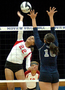 Elyria's No. 22 Alexis Middlebrooks spikes the ball to Lorain's No. 10 Kayla Lurry.