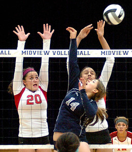 Lorain's No. 14 Serena Rodgriquez tris to pop a ball past Elyria's No. 20 Haley Looney and No. 22 Alexis Middlebrooks.