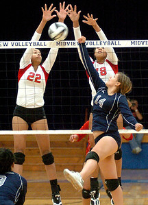 Elyria's No. 22 Alexis Middlebrooks and No. 18 Korey Middlebrooks block Lorain's No. 14 Serena Rodriguez's punched ball.