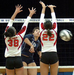 Lorain's No. 10 Kayla Lurry spikes the ball past Elyria's No. 38 Tyra Darden and No. 22 Alexis Middlebrooks.