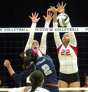 Elyria's No. 20 Haley Looney and No. 22 Alexis Middlebrooks block Lorain's No. 2 Raeven Bastock's spike.