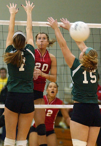 Elyria's Kristen Boros slams past Westlake 7 Hayley Brooks and 15 Coletta Carmichael in sectional volleyball Oct. 21.  Steve Manheim/CT