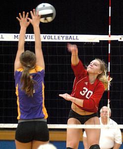 Elyria's #30 Emily Mandoke spikes the ball past Avon's #2 Olivia Boccabella.