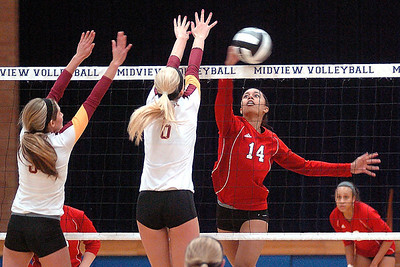Elyria's Mariah Johnson pops the ball past Avon Lake's Devan Rybarczyk, left, and Katie Mihalik. LINDA MURPHY/CHRONICLE