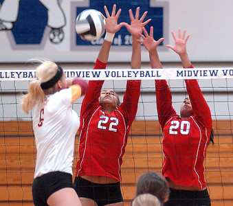 Avon Lake's Katie Mihalik tries to spike the ball past Elyria's Alexis Middlebrooks, center, and Tyra Darden. LINDA MURPHY/CHRONICLE