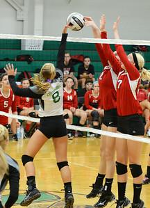 Columbia's Katlynn Krupinski pushes the ball over the net as Firelands' Dalaney Rogala, left, and Erica Wasem block. KRISTIN BAUER | CHRONICLE