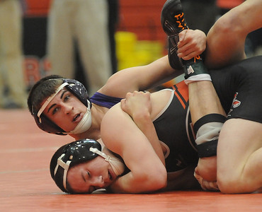 Keystone's Logan Stine defeats Elyria's Mike Dolan in the 138 weight class. STEVE MANHEIM/CHRONICLE