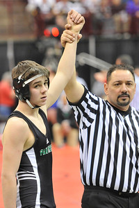 Stan Bleich of Elyria Catholic has his arm raised in victory in the consolation round in Div III yesterday in Columbus. DAVID RICHARD / CHRONICLE