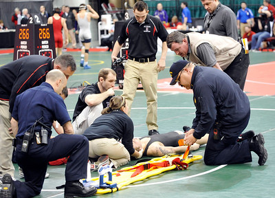 Elyria's Matt Canon is attended to on the mat after suffering an apparent concussion during his 120-pound match in the championship bracket yesterday against Uniontown Lake's Zac Carson. DAVID RICHARD / CHRONICLE