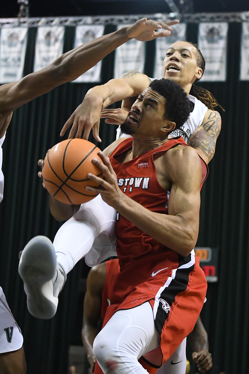 . Eric Bonzar�The Morning Journal<br> Youngstown State\'s Devin Haygood is fouled on his way to the basket by Cleveland State\'s Jamarcus Hairston, Jan. 1, 2018.