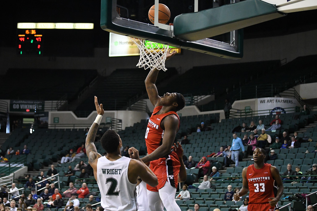 . Eric Bonzar�The Morning Journal<br> Youngstown State forward Tyree Robinson drops in a bucket over Cleveland State\'s Anthony Wright , Jan. 1, 2018.