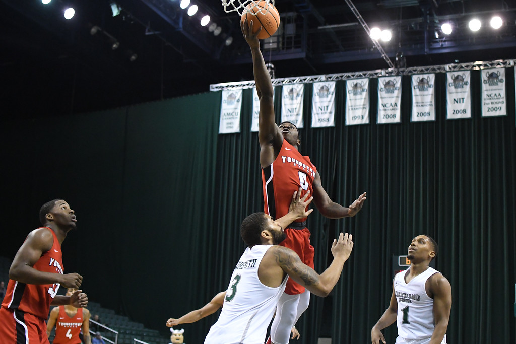 . Eric Bonzar�The Morning Journal<br> Youngstown State forward Tyree Robinson (0) hits a finger roll layup over Cleveland State\'s Dontel Highsmith (3), Jan. 1, 2018.
