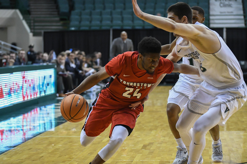 . Eric Bonzar�The Morning Journal<br> Youngstown State guard Cameron Morse (24) drives baseline past Cleveland State\'s Stefan Kenic (13), Jan. 1, 2018.