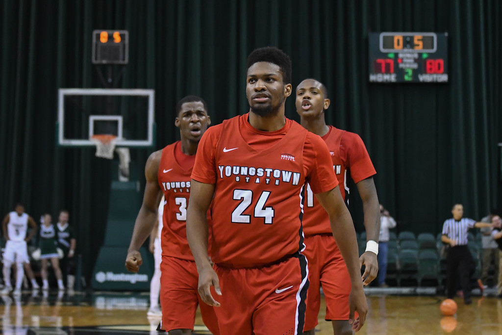 . Eric Bonzar�The Morning Journal<br> Flanked by forward Naz Bohannon, left, and guard Braun Hartfield, right, Youngstown State\'s Cameron Morse (24) struts to the other end of the court after sinking a 3-point basket with six-tenths of a second left in the game. The Penguins would go on to beat the Cleveland State Vikings, 80-77, Jan. 1, 2018.