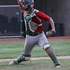 Ironmen catcher Luke Corrola fields a hit in front of the plate and throws to first for the out against the Bulldogs during the second game on Monday
