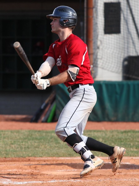 Cole Revels of the Ironmen lines a base hit against the Bulldogs during the first game on Monday at the Pipeyard
