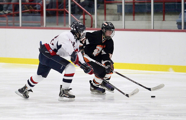 Record-Eagle/Keith King <br /> Cheboygan's Jake Elmore, right, skates with the puck against the Bay Reps' Quinn Lyman Wednesday, February 16, 2011 at the Kaliseum in Kalkaska.