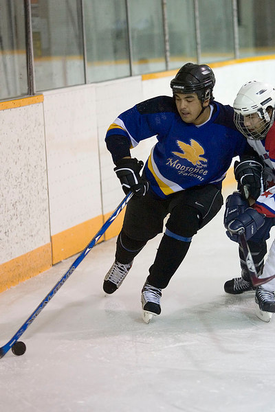 Richard Moore of the Falcons guides the puck past Jared Sackaney of the Selects.