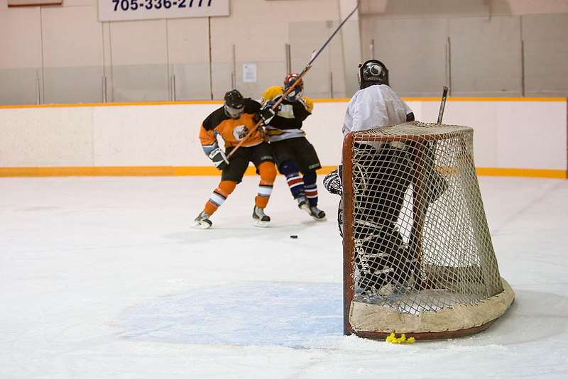 Sheldon Sackaney of the Polar Bears (left) and Desai Katapaytuk of the Bombardiers scrap over the puck to the side of Todd Reuben's Polar Bear net.