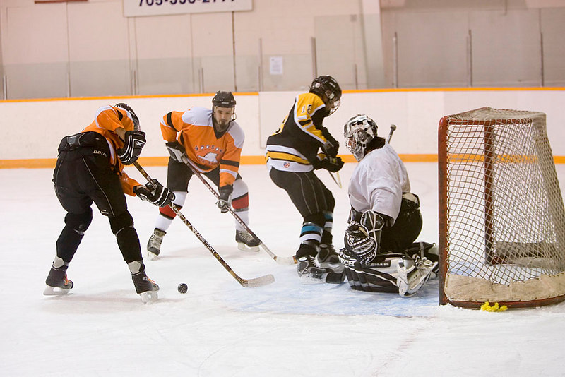 Willie Moore (9) and Clint Hamilton try to get puck away from their own net with Todd Reuben making a great save after Russell Williams (18) made a shot on goal.