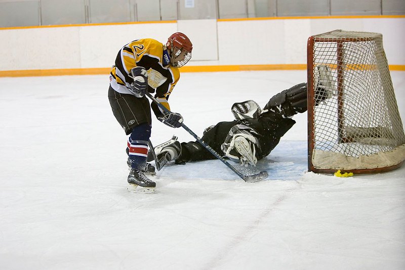 Desai Katapaytuk of the Bombardiers tries to get puck past Polar Bear goalie Todd Reuben.