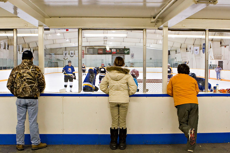 Spectators inside enclosed viewing area of Moosonee arena