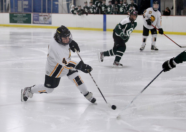 Record-Eagle/Keith King<br /> Traverse City Central's Derek Schrank (4) shoots the puck against Grand Rapids West Catholic during the second period Monday, February 25, 2013 in Howe Arena at the Grand Traverse County Civic Center.