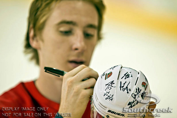 Miami (OH) University's Right Forward Max Cook (#19) signs a helmet during a team autograph session following their overtime shoot out of play at Miami University's Steve Cady Arena at the Goggin Ice Center in Oxford, Ohio, Saturday evening October 30, 2010. The Miami University Redhawks defeated the Lake Superior State University Lakers in a shoot out to end the 2010 regular season CCHA game.  (© James D. DeCamp / Southcreek Global Media)  | All Rights Reserved  | http://www.southcreekglobal.com | For all sales contact: sales@southcreekglobal.com | 1-800-934-5030