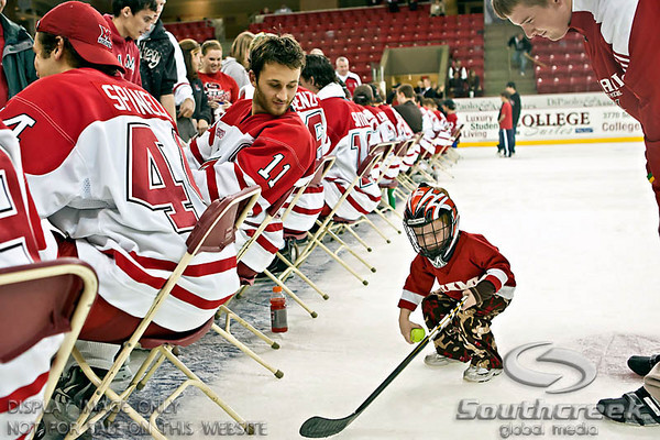 Miami (OH) University's Right Forward Carter Camper (#11) left, looks on as Miami (OH) University's Athletic Trainer Jason Eckerle helps his son Drew, 2 1/2 play behind the scenes of the teams autograph session following the overtime shoot at Miami University's Steve Cady Arena at the Goggin Ice Center in Oxford, Ohio, Saturday evening October 30, 2010. The Miami University Redhawks defeated the Lake Superior State University Lakers in a shoot out to end the 2010 regular season CCHA game.  (© James D. DeCamp / Southcreek Global Media)  | All Rights Reserved  | http://www.southcreekglobal.com | For all sales contact: sales@southcreekglobal.com | 1-800-934-5030